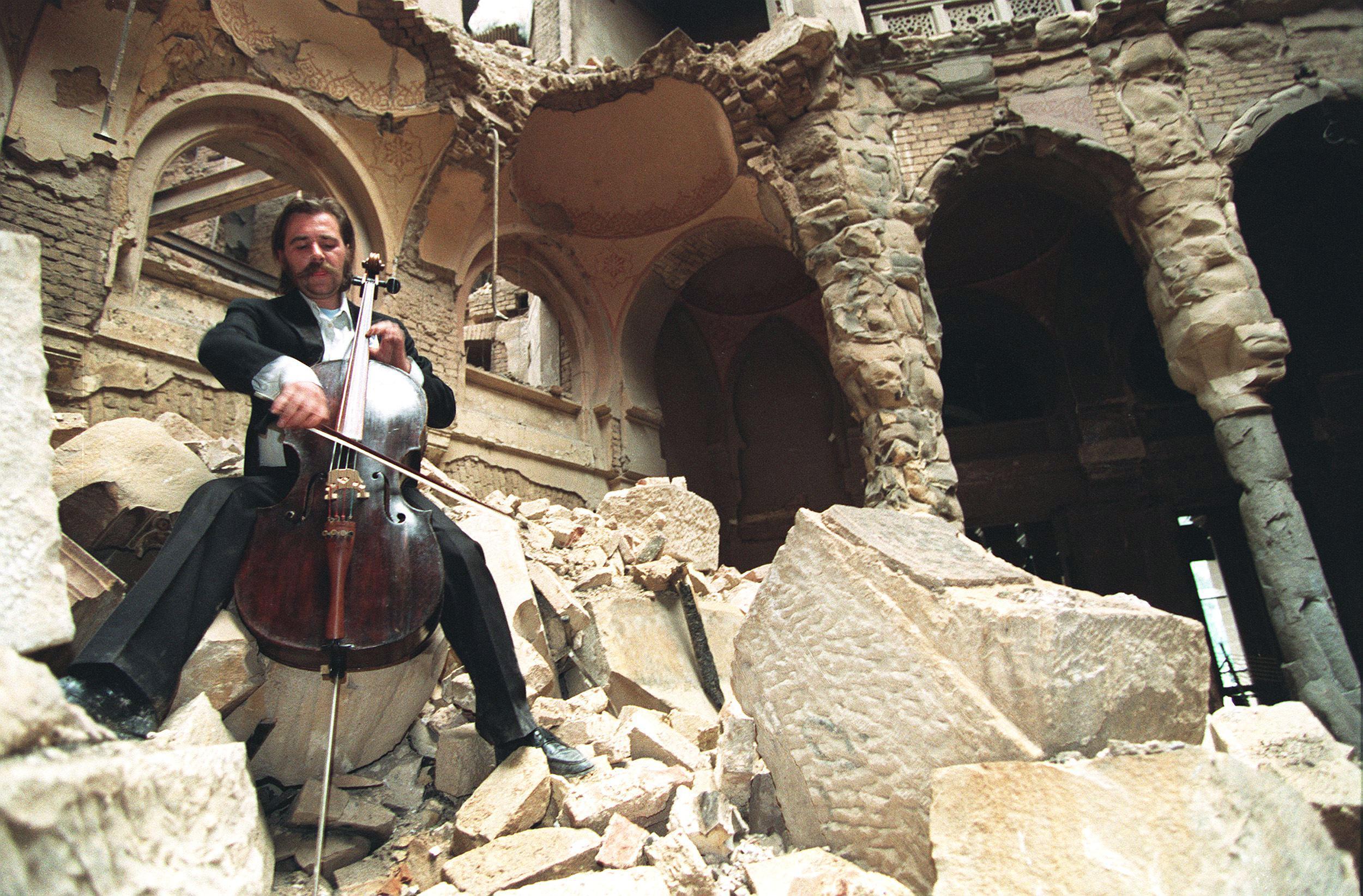 Il violoncellista Vedran Smailović suona tra le rovine della Vijećnica (1992).